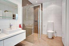 Dwie szklane ścianki w tej łazience tworzą nowoczesną kabinę prysznicową bez brodzika. Strefę natrysku zaznaczono dodatkowo brązową mozaiką, która kontrastuje z białymi kaflami na pozostałych ścianach. Wielkoformatowe płytki na podłodze są bezpieczne, bo ich matowa powierzchnia działa antypoślizgowo.