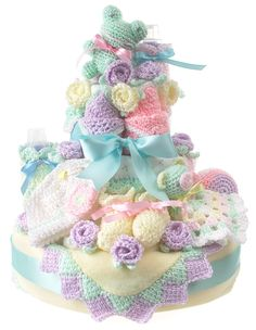 """Create a beautiful baby gift that doubles as the centerpiece for a baby shower. Soft and cuddly crocheted toys, bib, booties, edgings, bottle covers and more are combined with purchased cloth and disposable diapers (called """"nappies"""" in Europe) to create a gorgeous tiered cake that will be the highlight of a shower.This colorful cake is made by first arranging about 85 disposable diapers. Then the cake is """"frosted"""" with crochet-trimmed baby blankets, crochet baby toys, bibs, bot..."""