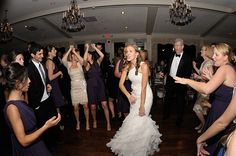Holding up her dramatic and elegant asymmetrical whtie organza dress with a ruffled mermaid skirt, a bride dances to the music of The Dreamscape Band at her wedding reception, held at the Oakmont Country Club, Pittsburgh. Several of her bridesmaids, wearing navy blue infinity dresses, surround her. The band kept the girls and the rest of the guests dancing all night long. http://www.dreamscapeband.com/weddings.html