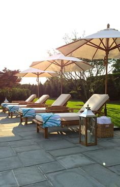 A tidy row of Frontgate's teak Cassara Chaise Lounges, accompanied by Half Moon Tables and Round Outdoor Market Umbrellas, create a spa-like space with equal amounts of sun and shade, plus smooth wheels for easy adjustments. | @indiahicks  for Hampton Designer Showhouse 2014