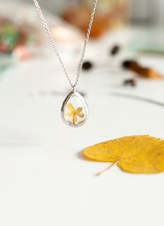 Inside this glass necklace lives a tiny yellow flower for you to carry