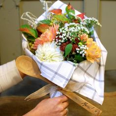 Wrap a bouquet of flowers in a dish towel and tie with a wooden spoon (great hostess gift idea)