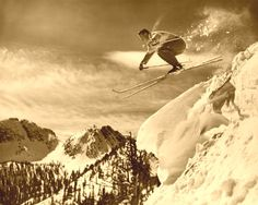 Skier jumping off a cornice on antique skis.