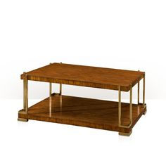 TA A Hyedua veneered cocktail table, the rectangular top above a two concealed veneered end slides, on square brass supports on a plinth base with brass feet.
