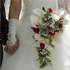 Boquet of red and ivory roses, accentuated by white lilies and trails of ivy.