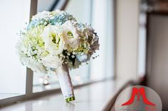 This mostly-white bridal bouquet with hints of blue is simple and stunning.