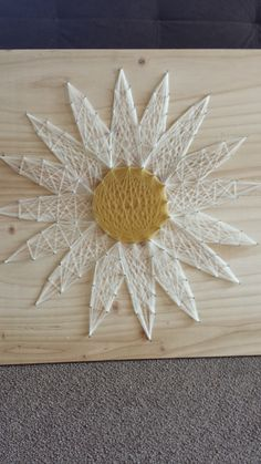 Our daisy string art wall decoration - just put some nails in a slab of wood and wrap colored string around the nails in cool patterns!