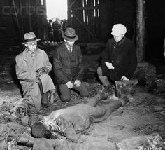 Original caption:Three German burgomasters grimly view the charred body of a victim of mass execution by Nazi at Gardelegen. American soldiers in background look in on scene. April 26, 1945