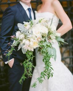 Blossom and Branch designed this cascading bouquet of seasonal roses, dusty miller, astrantia, jasmine vines, and protea.