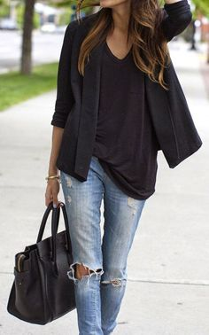 Black oversized blouse with black coat and black leather hand bag and blue casual stylish jeans the perfect fashion trend