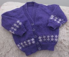 In acrylic and wool with a toning band of fairisle this 22 inch / 56 cm chest cardigan is £11.00 + £4.25 signed delivery