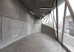 Cette structure en béton à facettes pourvue d'une façade en verre est perchée au-dessus d'une cour, elle sert d'extension à une maison située dans le quart