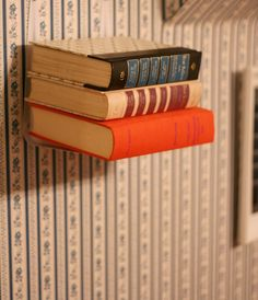 Love this floating bookshelf! Attach 2 angle brackets upside down to the wall and voila!
