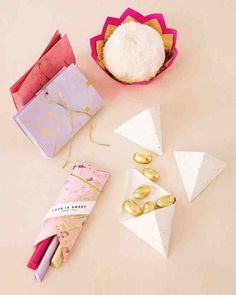 """When it comes to parting gifts, a cleverly packaged treat is sure to sweeten the deal. Plus, any of these containers can be made larger to accommodate whatever favors you fancy; just increase the size of the paper and folds used.Clockwise from left:A string-tied """"mini purse"""" is perfect for packing candies to go.Watch cupcakes or snowballs bloom inside a flowerlike dish.Slip slender sticks of chocolate in an envelope reminiscent of a pencil case or crayon box.Stack smaller snacks in…"""
