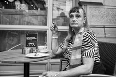 Lady sitting at an outside table of a restaurant shop drinking a coffee. Looking with an unhappy face into the world.