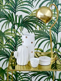 gold bar cart, gold table lamp, white and gold ceramics and leaf print wallpaper