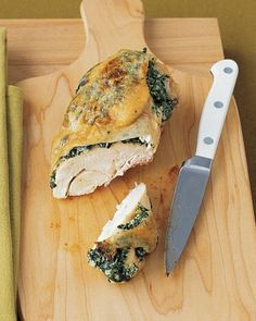Chicken Breasts Stuffed with Spinach and Ricotta - A mixture of ricotta cheese, minced garlic, and frozen chopped spinach is stuffed between the meat and skin of large, bone-in chicken breasts. Plum tomatoes are roasted alongside the chicken for an easy, flavorful side dish.
