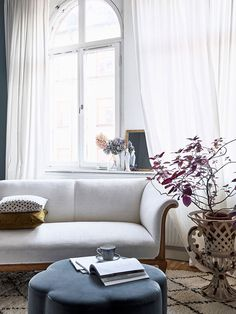 Bright living room with white couch and from floor to ceiling curtains