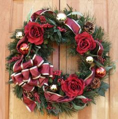 "Burgundy Rose Holdiay Wreath CR1048. Deck the halls this holiday season with our lovely Burgundy Christmas Wreath. 26"" Lush pine wreath decorated with burgundy roses, ribbon and ornaments."