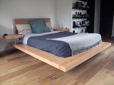 Cama baja en haya de diseño asimétrico y mesas de noche integradas a la base.