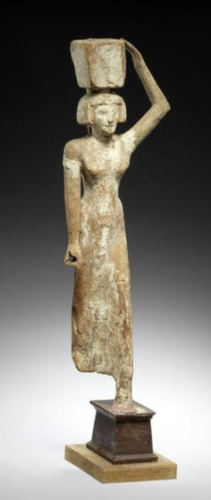 An Egyptian wood figure of a female offering-bearer  First Intermediate Period - Middle Kingdom, circa 2181-1797 B.C. Shown striding forward, her left leg advanced, wearing a short wig and sheath dress, her left arm raised to hold the offering basket balanced on her head, some gesso and polychrome remaining, 19in (48.2cm) high, mounted
