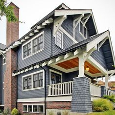 Wood shingles in slate blue, white trim  in fantastic craftsman details. The brick detailing is great. (Just a photo)