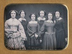 Different style dresses and different personalities, but resembling each other greatly! I venture the three on the right front are sisters, emphasizing their special relationship by linking. Ca. 1850