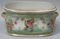 Staffordshire pottery green ground footbath, decorated with floral sprays flanked by cream glazed gilt enriched loop handles.