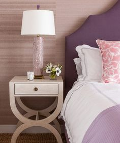 Pink and purple bedroom features a wall clad in light brown grasscloth wallpaper lined with a purple headboard on bed dressed in white and gray scalloped bedding, pink pillows and a purple throw blanket next to a cream nightstand with gold knobs and a purple faux bois lamp.