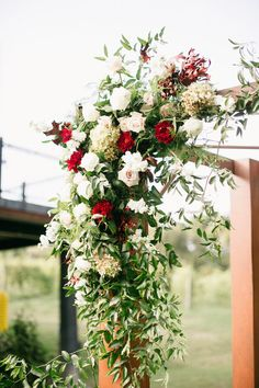 Flowers for a wedding ceremony arch - outdoor summer wedding with burgundy, white, and blush roses and greenery #weddingflowers #ceremonyideas #summerwedding #virginiaweddingflorist