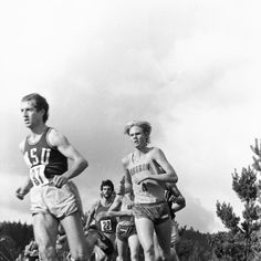 Black and white photo of University of Oregon cross country runner Greg Erwin striding among a pack of competitors, on his way to a seventh place finish at the Northern Division Championships held at Lane Community College in 1979. ©University of Oregon Libraries - Special Collections and University Archives