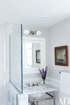 In a bath, the light fixture, washstand and fittings, and marble tiles are all by Waterworks | http://archdigest.com