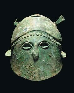 Pseudo-Corinthian helmet, 5th century B.C. With contoured crown, false eyes recessed for inlays, the nose and curling hair locks over the brow moulded in relief, flange at rear, remains of attachment plates for plume and crest holders, 18.7 cm high. Private collection, from Christie's auction