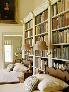 Library Bedroom :: A book collection on shelves stands behind the beds in this library guest room. Swing-arm lamps offer a reading light for all of the treasures waiting to be found in books.
