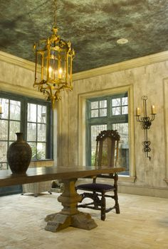 The walls are a faux stained concrete, the crown,baseboards and window casings are a faux limestone. The windows are a faux bronze patina, and the ceiling is a faux tin embossed tile painted to look like a distressed weathered bronze.  Interior Design: Patrick Sutton