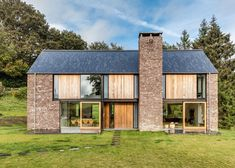 This barn-chic modern gable home is full of texture and pattern with slate roof tiles, masonry walls, a large stone chimney, wood panels and large glass openings.
