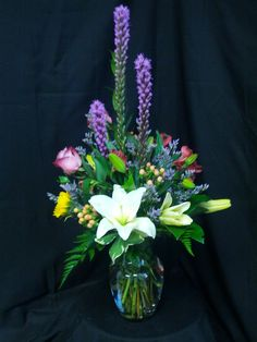 This arrangement is in a clear C999 and has 3 liatris, 2 roses, 3 hypericum, 1 sunflower, 2 alstromeria, 2 asiatis lilly, 2 limonium, leather and salal.