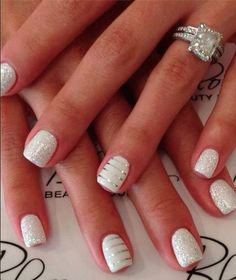 A matte white and silver coated nail art design making use of metallic silver strips as design on the top.