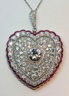 diamond and ruby heart pendant A large Edwardian platinum pendant the outer border set with calibre cut rubies, a border of old cut diamonds, a heart shaped open border, the centre of the heart pave set with old cut diamonds with in the middle an old cut diamond (app. 2.25 carats and app. 8 carats in total), Nehterlands, circa 1910, with a beautiful long platinum and diamond chain.