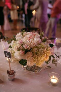 Wedding table centerpiece with white roses and hydrangeas and with ...