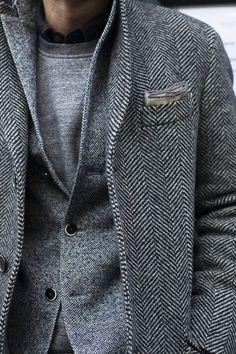 Den Look kaufen: https://lookastic.de/herrenmode/wie-kombinieren/mantel-sakko-pullover-mit-rundhalsausschnitt-langarmhemd-einstecktuch/1436 — Grauer Mantel mit Fischgrätenmuster — Graues Einstecktuch — Grauer Pullover mit Rundhalsausschnitt — Schwarzes Langarmhemd — Graues Wollsakko mit Fischgrätenmuster
