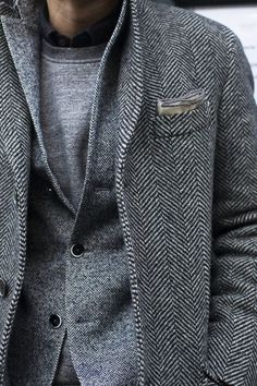 Shop this look for $900:  http://lookastic.com/men/looks/overcoat-and-blazer-and-pocket-square-and-crew-neck-sweater-and-longsleeve-shirt/1436  — Grey Herringbone Overcoat  — Grey Herringbone Blazer  — Grey Pocket Square  — Grey Crew-neck Sweater  — Black Longsleeve Shirt