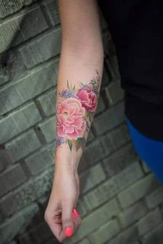 This pink flower tattoo is a good design for women who want to tattoo their forearms with something beautiful and attractive. The floral design appears large, but also colorful and soft. The tattoo also looks great with various hand accessories, particularly floral ones. #tattoofriday #tattoos #tattooart #tattoodesign #tattooidea