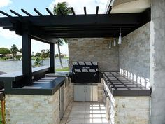 Built-in BBQ Pergola Stacked Stone Outdoor Kitchen by Outdoor Kitchens & Living of Florida