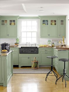 This spacious and sunny kitchen is very inviting with its hardwood flooring, pale green cabinetry, apron front sink, and the flexible seating offered. Not crazy about the backless industrial stools.