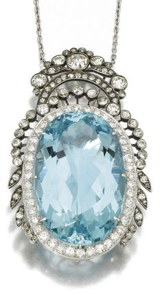 Art Deco or Edwardian aquamarine and diamond pendant, circa 1910. It features a lively, oval-cut aquamarine within a frame of circular cut diamonds and wreathed in floral and foliate details. 20 inch chain. Via Diamonds in the Library.