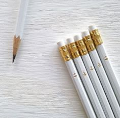 an anchor is hand foil stamped in gold on #2 white pencils with a white eraser and gold ferrule.