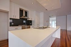 White modern kitchen with black glass backsplash and white island with sink