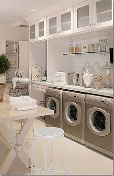 Awesome laundry room- Light, bright, great table, glass ware, storage tin and laundry basket, antiqued pot and plant.