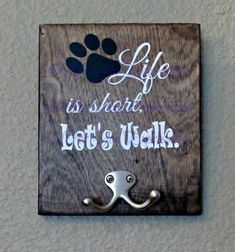"""""""Life is short, let's walk"""". Wooden sign with Dog leash holder. Custom made just for you and your furry exercise partner. Pick your color of vinyl for the words and paw print. Also pick your stain color for the wooden board. #dogsayings"""